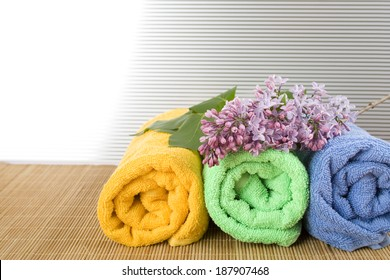 Colored towels folded lie next to them a branch of lilac