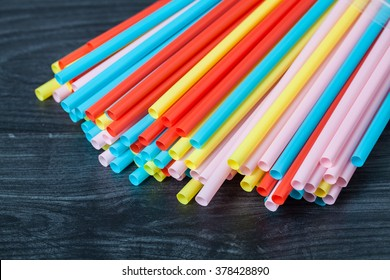 colored tubules for juice and cocktails on black wooden table