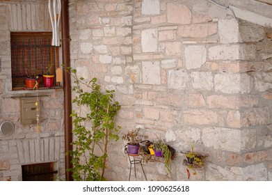 Colored vases on the wall of a  medieval building (Collepino, Umbria, Italy)