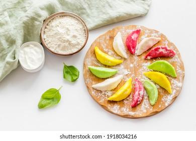 Farbige Gemüsedummlinge oder Ravioli auf Zerspanungsbrett
