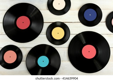 colored vinyl plate on white wooden background