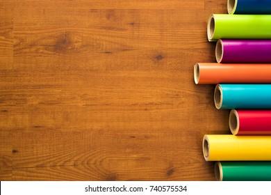 Colored vinyl rolls over wooden background