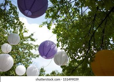 Colored wedding decorations hang from the trees at a wedding