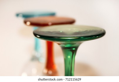 Colored wine glasses stand on a white background