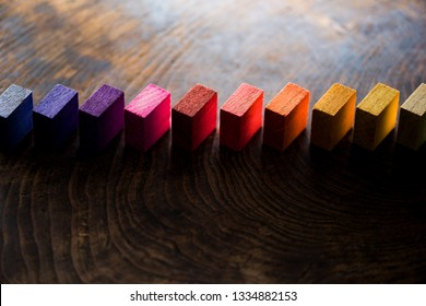 Colored wooden blocks aligned on old vintage wooden table. For something with concept of variations or diversity. Plenty of copyspace. Shallow depth of field.