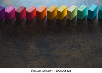 Colored wooden blocks diagonally aligned on old vintage wooden table. For something with concept of variations or diversity.