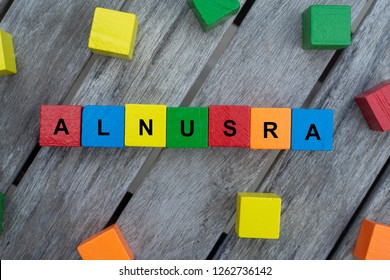 colored wooden cubes with letters. the word alnusra is displayed, abstract illustration