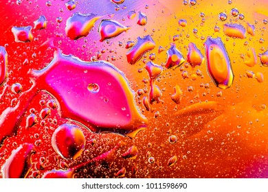Colorful abstract background. Water drops rainbow colors on glass. Amazing abstract water drops on glass textture or background.
