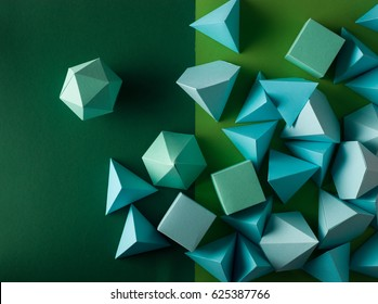 Colorful abstract geometric background with three-dimensional solid figures. Pyramid Dodecahedron prism rectangular cube arranged on green paper.