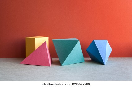 Colorful abstract geometrical composition. Three-dimensional prism pyramid tetrahedron rectangular cube objects on red gray paper background. Yellow blue pink green colored solid figures, soft focus