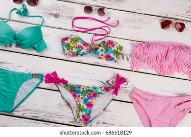 Colorful accessories for bathing. Different swimming costumes and sunglasses on white wooden background.
