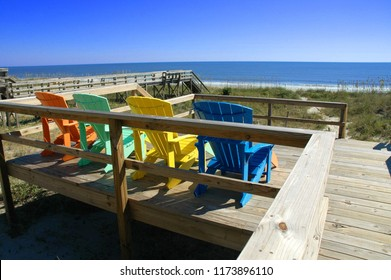 Colorful Adirondack chairs at the beach.
