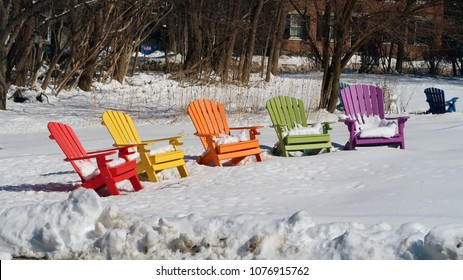 Colorful adirondack chairs in the snow.