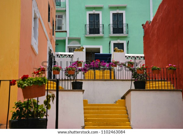 Coloridas casas de adobe con paredes de estuco y macetas de flores de geranio en la Avenida Hidalgo en Atlixco, Puebla México.