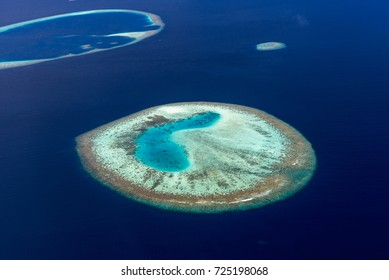 Colorful aerial photo of small island in Maldives atolls and deep blue sea