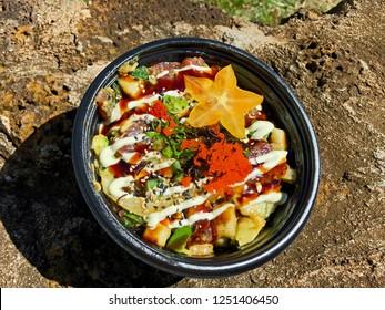 Colorful Ahi (Tuna) Poke Bowl with cucumbers, avocado, aioli, sesame seeds, flying fish roe (tobiko), green onions, wasabi, and starfish