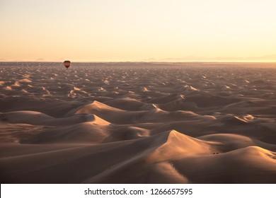 Colorful air balloons flying during dawn over desert dunes. Dubai, UAE.