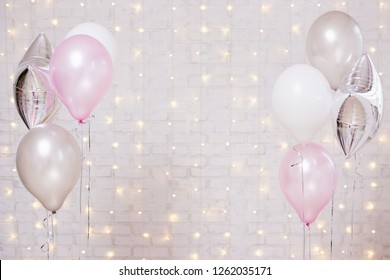 colorful air balloons over white brick wall background with lights