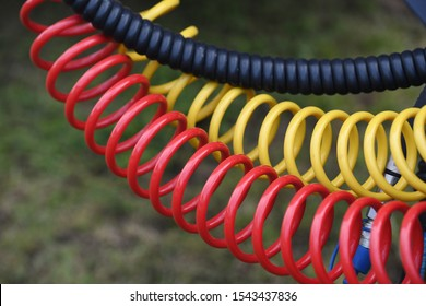Colorful air pressure hoses in front of a green background.