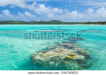 The colorful Aitutaki lagoon spotted by coral reef, in the middle of the South Pacific Ocean. Aitutaki atoll, Cook Islands.