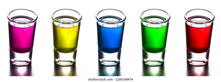 Colorful alcohol in transparent glass vodka shots isolated on white in a row.