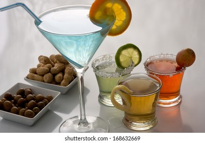 Colorful alcoholic coctails with olives and peanuts snacks.