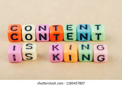Colorful alphabet letter dice text on desk, spelling CONTENT IS KING