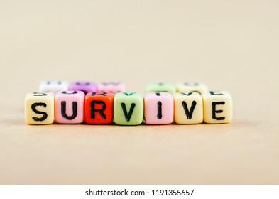 Colorful alphabet letter dice text on desk, spelling SURVIVE