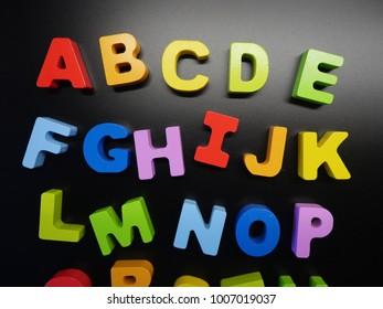 Colorful alphabet on black background, kids learning concept