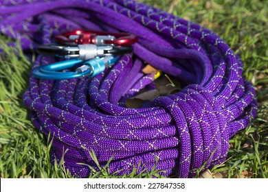 Colorful alpine climbing rope dropped on the green grass and decorated with some climbing tools