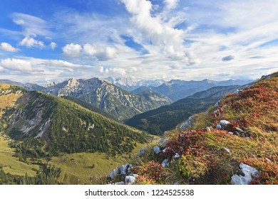 Colorful alpine landscape with rocky mountains, red and green grass and forests in autumn in the Ammergau Alps (Bavaria, Germany). Zugspitze, highest mountain of Germany, in the background