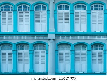Colorful antique blue turquoise wooden window Colonial style architecture building on turquoise cement wall vintage style in Singapore