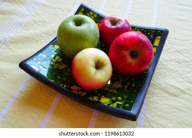 colorful apples on the decorative bowl on the table, autumn harvest from garden