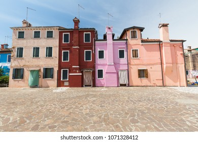 The colorful architecture of the sunny Island of Burano, a tourist attraction near Venice, Italy, which shows the harmony, joyful approach and lifestyle