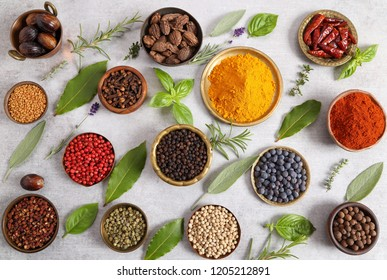 Colorful and aromatic herbs and spices on a gray ceramic background. Top view.