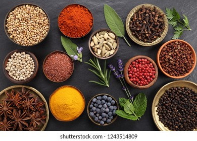 Colorful and aromatic herbs and spices on a black ceramic background. Top view.