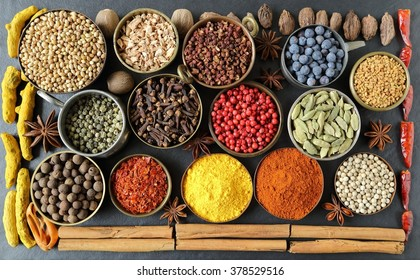 Colorful, aromatic spices in bowls on the black ceramic background.
