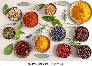 Colorful, aromatic spices and fresh herbs on a light background. Top view.