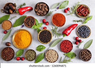 Colorful, aromatic spices and fresh herbs on a grey background. Top view.
