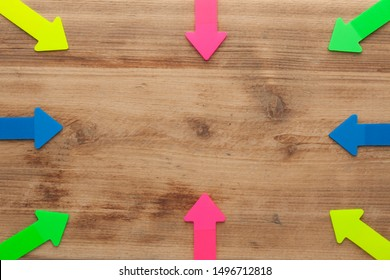 Colorful arrows pointing to center on natural wooden surface old desk texture background, wood grunge wall pattern.