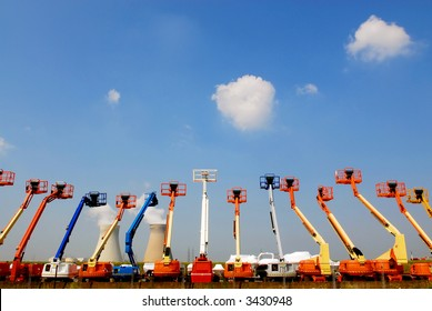 colorful articulating construction boom lifts with power plant on background