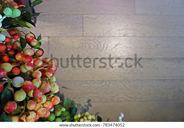 Colorful artificial fruits for decoration.  Selective focus on the center of the fruits and the wooden background is blurred.