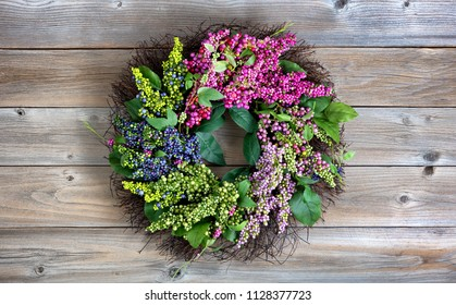 Colorful artificial wreath made of flowers and leaves on vintage wood background