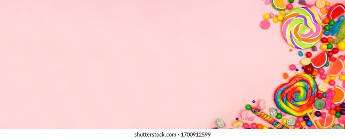 Des bonbons colorés et assortis. Bordure d'angle de vue de dessus sur fond grunge rose.