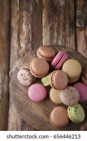 Colorful assorted macaroons on brown wooden board on brown wooden background with space for text. Rustic style. Overhead shot