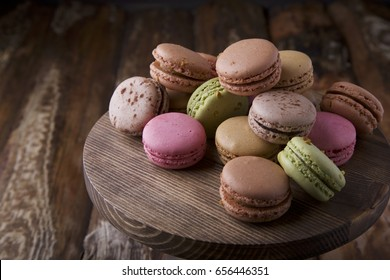 Colorful assorted macaroons on brown wooden board on brown wooden background with space for text. Rustic style