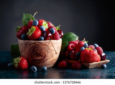 Colorful assorted mix of strawberry, blueberry, raspberry and sweet cherry in studio on dark background.
