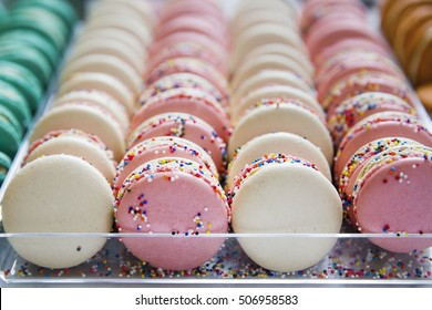 Colorful assortment of french macaron pastry cookies covered in rainbow sprinkles