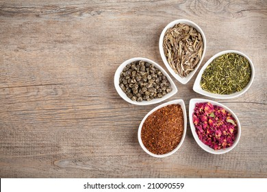 A colorful assortment of loose teas in petal shaped bowls on a wooden background with copyspace