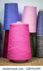 Colorful assortment of vivid colors of cotton spools on cardboard cones for use in the knitwear and garment industry
